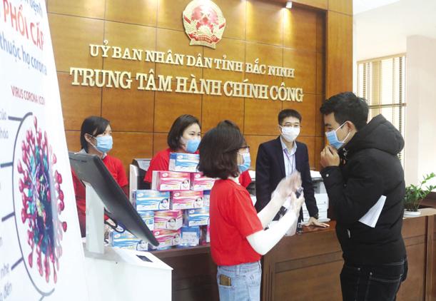 Xịt sát khuẩn và phát khẩu trang cho người dân tại Trung tâm Hành chính Công tỉnh